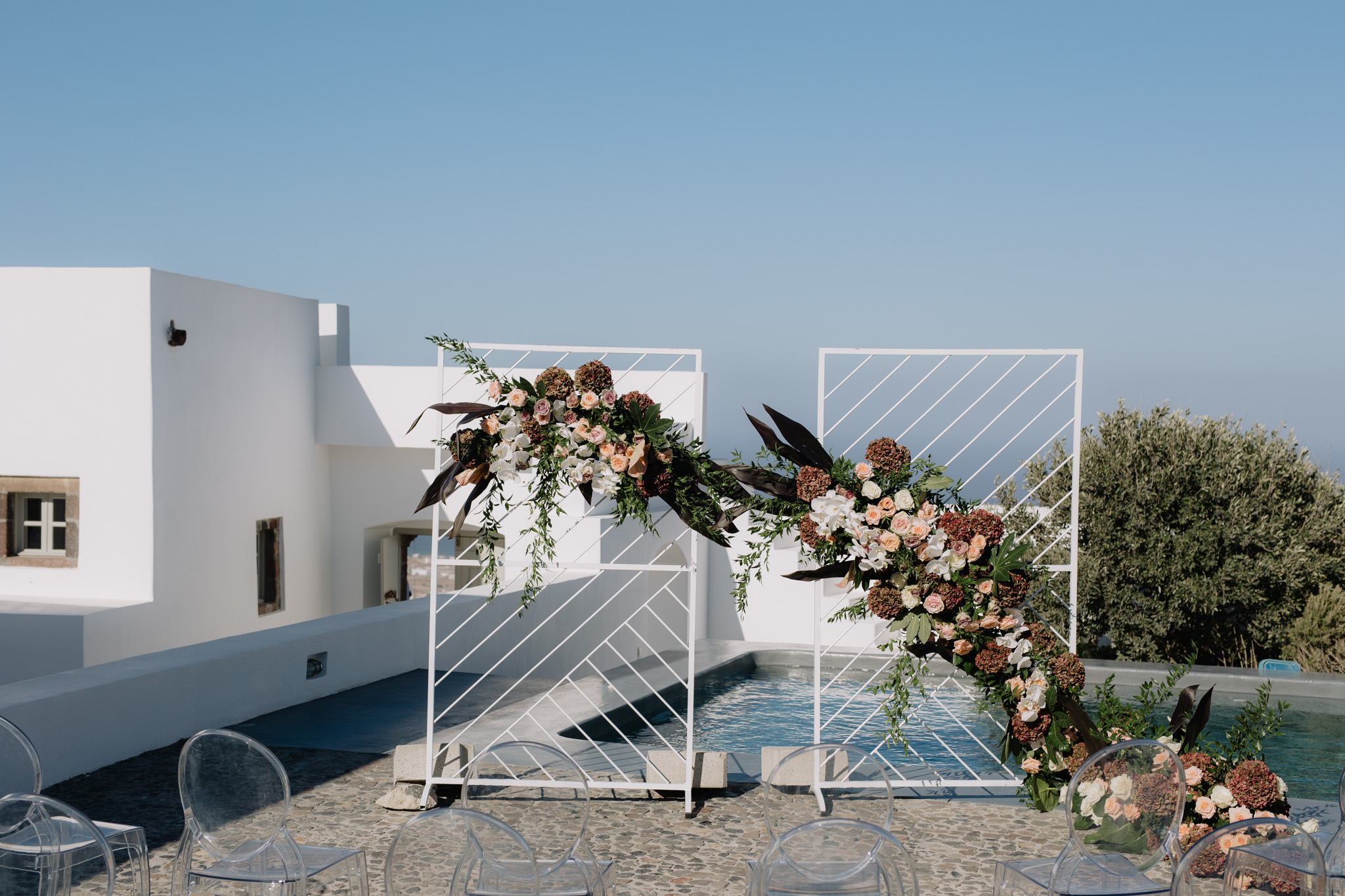 Santorini wedding photographer ceremony arch flowers bouquets orchids ghost chairs villa fabrica