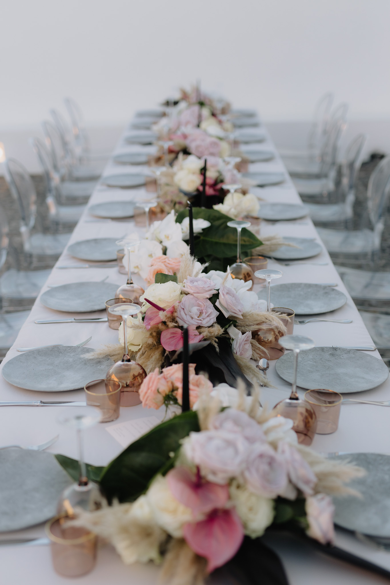 Santorini wedding photographer reception flowers table setting villa fabrica orchids dinner styling ghost chairs